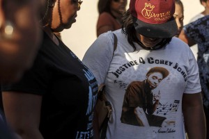 FILE- In this Oct. 20, 2015, file photo, friends and family of Corey Jones attend a news conference led by Bishop Sylvester Banks, Sr., grandfather of Jones, outside Bible Church of God in Boynton Beach, Fla. A T-shirt honoring Jones was worn by some in attendance. Nouman Raja, a fired Florida police officer, was charged Wednesday, June 1, 2016, in the fatal shooting of Jones, a legally armed black musician who had apparently thrown his weapon and was running away when the lethal shot was fired, prosecutors and court documents said. (Thomas Cordy/The Palm Beach Post via AP, File) MAGS OUT; TV OUT; NO SALES; MANDATORY CREDIT