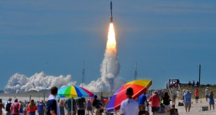 Hundreds of people pack the Canaveral national seashore's Playalinda Beach as a United Launch Alliance Atlas V rocket, carrying a U.S. Navy communications satellite, lifts off from Complex 41 at the Cape Canaveral Air Force Station, Friday, June 24, 2016, in Cape Canaveral, Fla. The satellite is designed to significantly improve ground communications for U.S. forces on the move.  (Craig Rubadoux/Florida Today via AP)