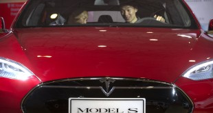 "FILE - In this file photo, a man sits behind the steering wheel of a Tesla Model S electric car. Federal officials say the driver of a Tesla S sports car using the vehicle's ""autopilot"" automated driving system was killed May 7 in Williston, Fla. in a collision with a truck, the first U.S. self-driving car fatality. The National Highway Traffic Safety Administration said preliminary reports indicate the crash occurred when a tractor-trailer made a left turn in front of the Tesla at a highway intersection. NHTSA said the Tesla driver died due to injuries sustained in the crash.(AP Photo/Mark Schiefelbein, File)"
