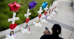 Crosses, one for each victim, line a walkway as a memorial to those killed in the Pulse nightclub mass shooting a few blocks from the club early Friday, June 17, 2016, in Orlando, Fla. Experts say it's too soon to gauge whether a week of horrific news out of Orlando will hurt tourism there. But travel agents are not seeing widespread cancellations, and many travelers say they're committed to their theme park vacations. (AP Photo/David Goldman)