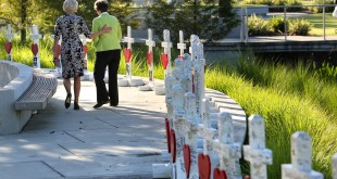 On the one-month anniversary of the Pulse nightclub massacre in July, Orlando city commissioner Patty Sheehan (right) and a friend take a last look at crosses honoring the 49 victims. A survivor of the attack wants a temporary stop to the distribution of money raised for the victims until an audit is done. (File/AP)