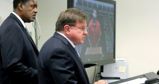 Attorneys from left to right, Dohn Williams and Longworth Butler represent murder suspect Dayonte Resiles as he appears via video conference before Broward Judge Michael Davis, in Fort Lauderdale, Fla., Thursday, July 21, 2016.  After nearly a week on the lam, Resiles, who slipped from his shackles and bolted from a crowded South Florida courtroom in a meticulous escape plot involving multiple accomplices was captured at a nondescript motel, authorities said Thursday. (Mike Stocker/South Florida Sun-Sentinel via AP)