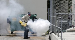 A Miami-Dade County mosquito control worker sprays around a school in the Wynwood area of Miami on Monday, Aug. 1, 2016. The CDC has issued a new advisory that says pregnant women should not travel a Zika-stricken part of Miami, and pregnant women who live there should take steps to prevent mosquito bites and sexual spread of the virus. (AP Photo/Alan Diaz)