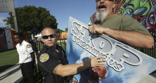 A Miami police officer holds back protestor Judd Allison (right) as Florida Gov. Rick Scott leaves a news conference at Wynwood Walls on Monday in the Wynwood neighborhood of Miami. The governor said the arts district is no longer considered a zone of active Zika transmission. It has been 45 days since the last Zika detection. Allison was protesting the use of the pesticide naled, which was used in the area to combat Zika. (AP Photo/Lynne Sladky)