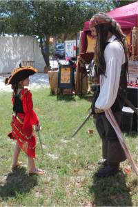 "Pirate-in-training Tierney Jones, of Williston, (left) practices her footwork with J. J. ""Captain Jack Sparrow"" Minshull (right) at the 4th Annual Cedar Key Pirate Fest on Friday. Minshull, of Margate, is one of dozens of ""pirates"" who are celebrating in Cedar Key this weekend. (Jordanne Laurito/WUFT News)"