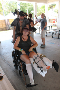 """Jeanie Hooper, of Bradenton, dislocated and broke multiple bones in her lower leg while helping clean up Cedar Key after Hurricane Hermine. She will not walk for at least six months, but came to enjoy the Pirate Fest. """"This is our home away from home,"""" she said (Jordanne Laurito/WUFT News)"""