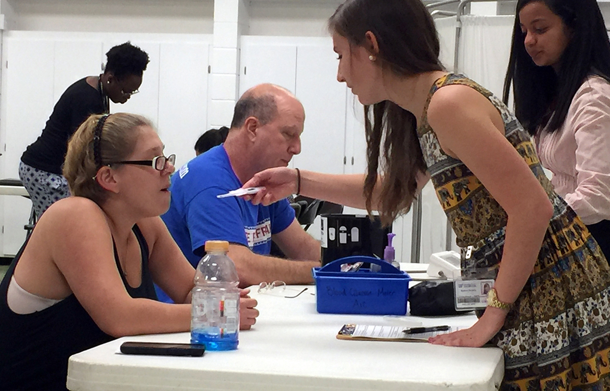 Cassie Hickman (right) gets her temperature taken at the Equal Access Clinic on Wednesday evening at Bartley Temple United Methodist Church in East Gainesville. The clinic also serves East Gainesville from 6 p.m. to 9 p.m. on Tuesdays at Eastside Clinic on Waldo Road. (Briana Erickson/WUFT News)