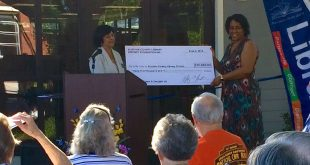Shaney Livingston, the High Springs Library Director, holds a check at the ribbon cutting ceremony of the branch's newly renovated library Saturday. The check, from Alachua County Library District Foundation, helped fund a portion of the city's renovated library.