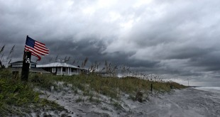 Storm clouds move along Atlantic Beach and gusty winds blow an American flag as Hurricane Hermine was downgraded to a tropical storm after making landfall on the gulf coast of Florida, Friday, Sept. 2, 2016. (Bob Mack /The Florida Times-Union via AP)