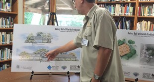 Silver River Museum Director Scott Mitchell points to renderings of the museum's expansion that will hold 30,000 new pieces. The expansion is expected to be completed in three years. (Maggie Lorenz/WUFT News)