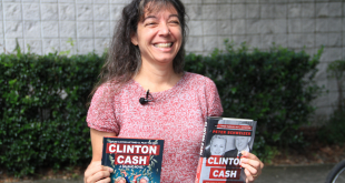 "Ann Lhota, of Newberry, Florida, holds up the book and graphic-novel versions of ""Clinton Cash"" outside Alachua County's Newberry library on Monday. Lhota said she's upset by the county library system's refusal to purchase the graphic novel. (Cecilia Mazanec/WUFT News)"