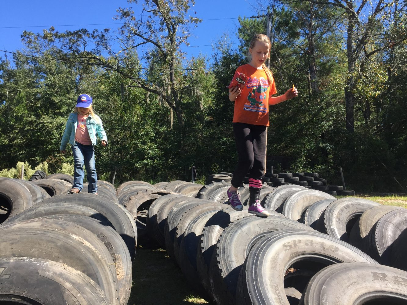 Layla, 7, (left) and 11-year-old Codi play on used tires, stacked by size. They came out with their parents to help organize the tires for Bronson's Hot Chick's Earthship Project. (Sara Girard/WUFT)