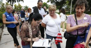 Cecilia Paz, foreground, fills out a new voter registration form because of a change of address, as she waits in line to attend a rally for Democratic presidential candidate Hillary Clinton and former vice president Al Gore, Tuesday, Oct. 11, 2016, in Miami. (AP Photo/Wilfredo Lee)
