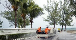 Landscapers ride in a truck along a stretch of road that's partially flooded from rain triggered by the arrival of Hurricane Matthew, in the eastern district of Nassau, Bahamas, Wednesday, Oct. 5, 2016. Forecasters said the storm was on track to roll directly over the capital city before nearing the Florida coast. (AP Photo/Craig Lenihan)