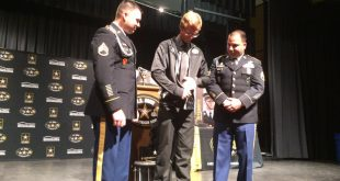 Buchholz High School senior Ben Harbaugh (middle) zips up the official jacket of the U.S. Army All-American Marching Band in a ceremony Monday at the school. Ben was one of 125 nationwide to be selected to perform in the band during halftime of the U.S. Army All-American Bowl. (Maggie Lorenz/WUFT News)