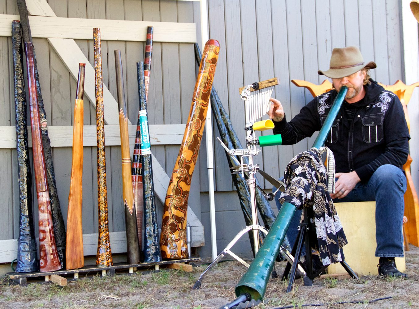 Lindsey Dank plays a didgeridoo at the festival Saturday. Dank said he enjoys interacting with the children and teaching them how to play. (Vedrana Damjanovic/WUFT News)