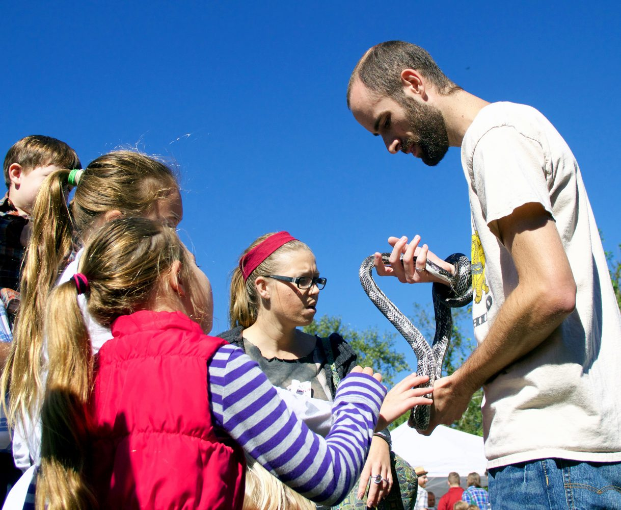 Ian Hahus, an agricultural engineering Ph.D. student at the University of Florida, holds a 6-foot-long grey rat snake named Hawkeye on Saturday while children look on and pet the snake. (Vedrana Damjanovic/WUFT News)
