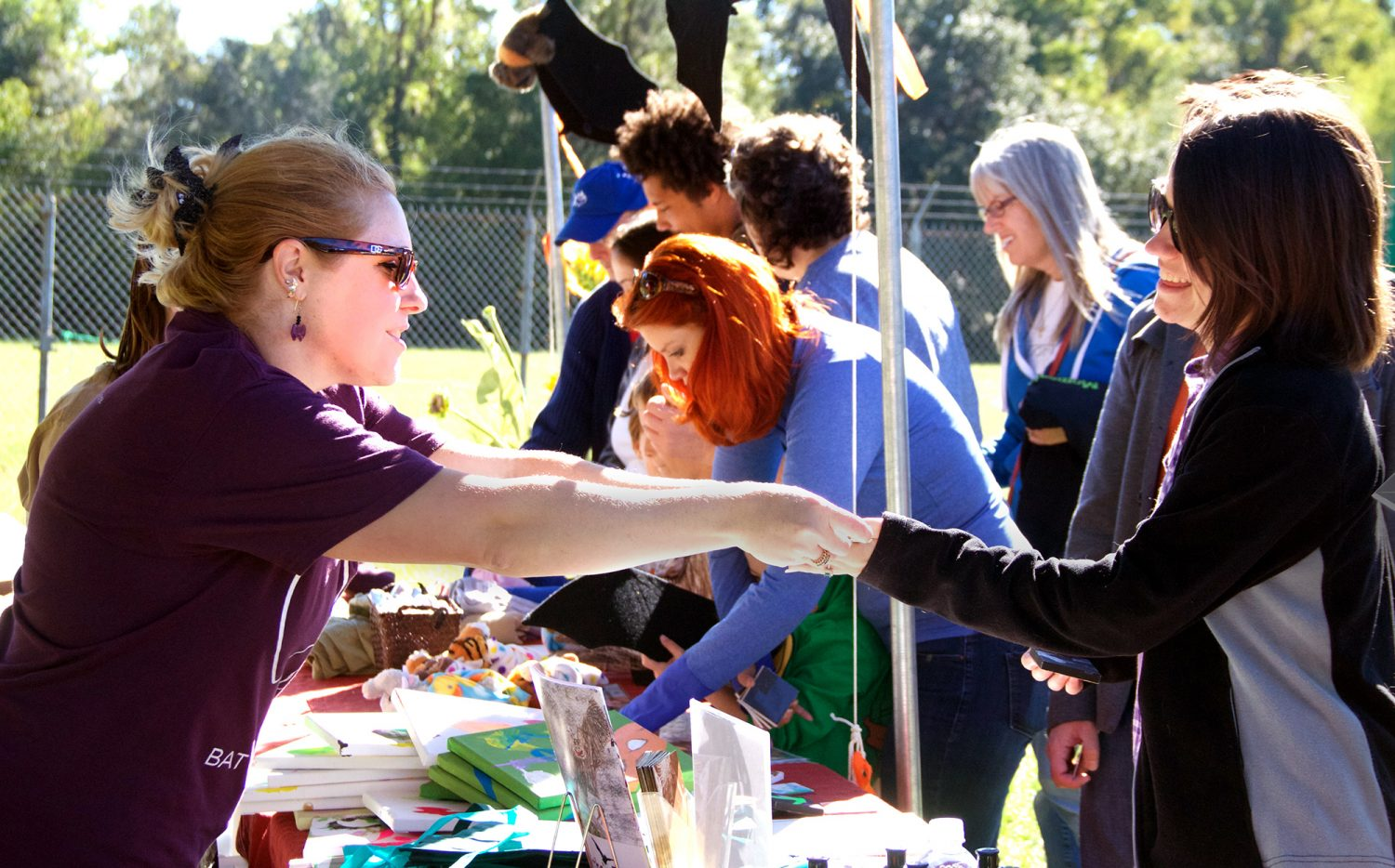 Tracy Pope (left), a program coordinator at Lubee, sells bat toys, crafts and arts at Saturday's festival. (Vedrana Damjanovic/WUFT News)