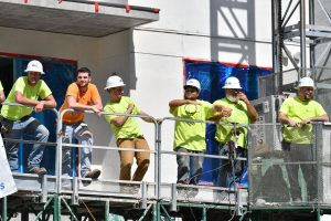 A group of construction workers take a break to watch the UF Homecoming Parade. (Grace King/WUFT News)