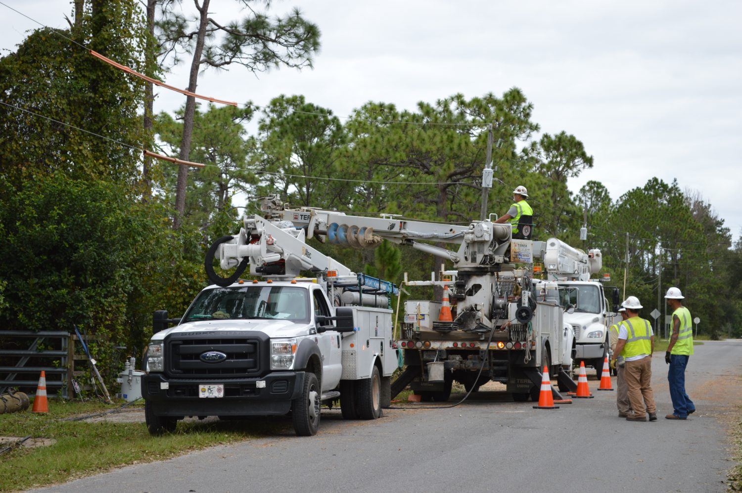 Workers fix a power line outside the Palatka home of Larry Murrow. Murrow said he hasn't had power since Friday. (Cecilia Mazanec/WUFT News)