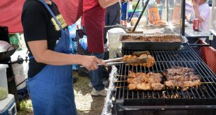 Moi Mateny flips over grilled chicken on a stick at a tent that sells Thai food. (Nicole Dan/WUFT News)