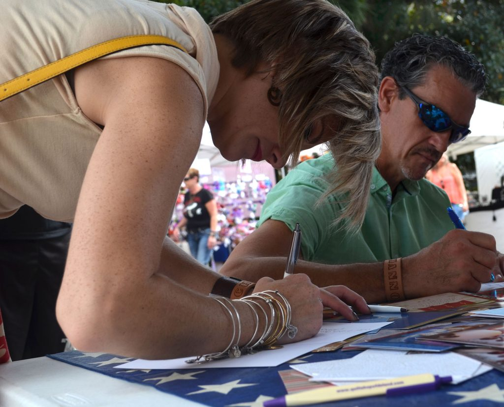 Shannon Bidgood and Charles Passon write Christmas cards to soldiers. (Nicole Dan/WUFT News)