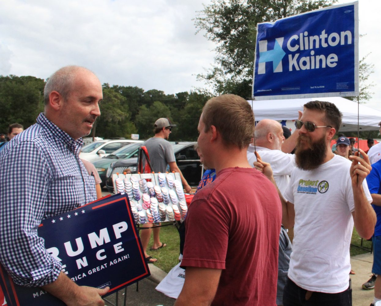 Rich Denmark holds a Clinton/Kaine sign as people leave the arena Wednesday afternoon. Even though no protestors were removed from the venue during the rally, the audience booed requests from the stage not to harm any who might try to disrupt the proceedings.