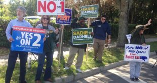 Political supporters hold election signs outside the Alachua County Supervisor of Elections Office in October during early voting. About 800,000 vote-by-mail ballots hadn't been returned as of Sunday. (File/WUFT News)