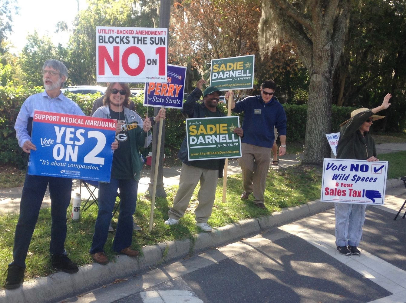 """Political supporters hold election signs Monday outside the Alachua County Supervisor of Elections Office. """"A lot of people have an opportunity here [to early vote] but not outside of the city, so this is an important place to be,"""" said Joe Fluriach, 26 (unseen holding the Keith Perry sign). (Cecilia Mazanec/WUFT News)"""