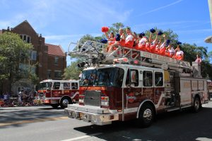 University of Florida cheerleaders wave to the crowd from the top of a Gainesville Fire Department truck. (Jordanne Laurito/WUFT News)