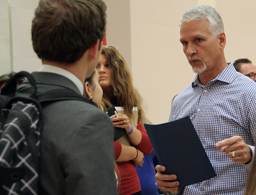 Keith Perry talks to a debate attendee Tuesday night. (Catie Flatley/WUFT News)