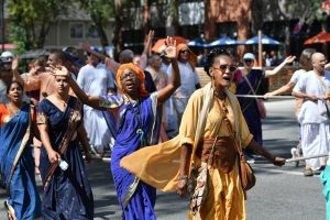 Members of the Hare Krishna movement sing their way down University Avenue during the parade. (Grace King/WUFT News)