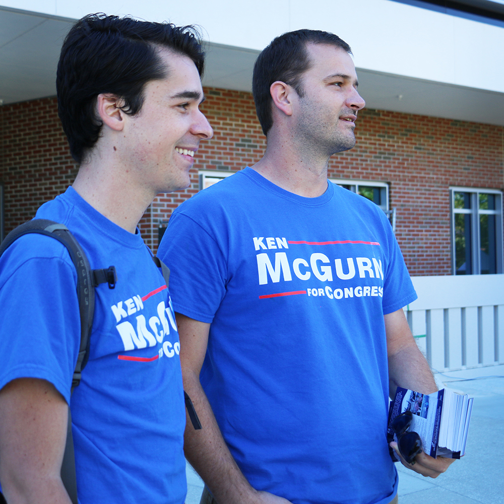 Bryan Eastman (left), 27, and Jason Stanford, 40, hand out flyers for congressional candidate Ken McGurn. Stanford said the issue most important to him this election cycle was climate change because being a Florida native made the issue of rising sea levels feel more urgent.