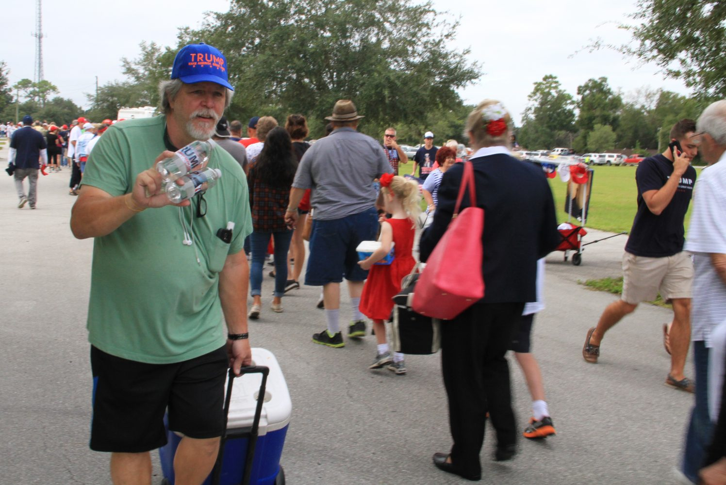 A man, who chose to be identified as Mike Campaign HQ, sells bottles of water to people waiting in line to see Donald Trump on Wednesday morning. The line to get into the event began to form before 7 a.m., and people continued to enter the venue until after 2 p.m.