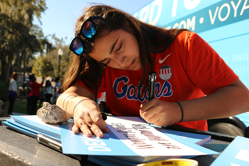 """Daniella Mora, 19, writes """"Women's rights are human rights,"""" on a poster stating why she is a Democrat, and said it was the most empowering quote of Hillary Clinton's campaign. Growing up Latina, Mora said she experienced discrimination and hopes that if Clinton were elected, it would help minimize racist rhetoric in the country."""