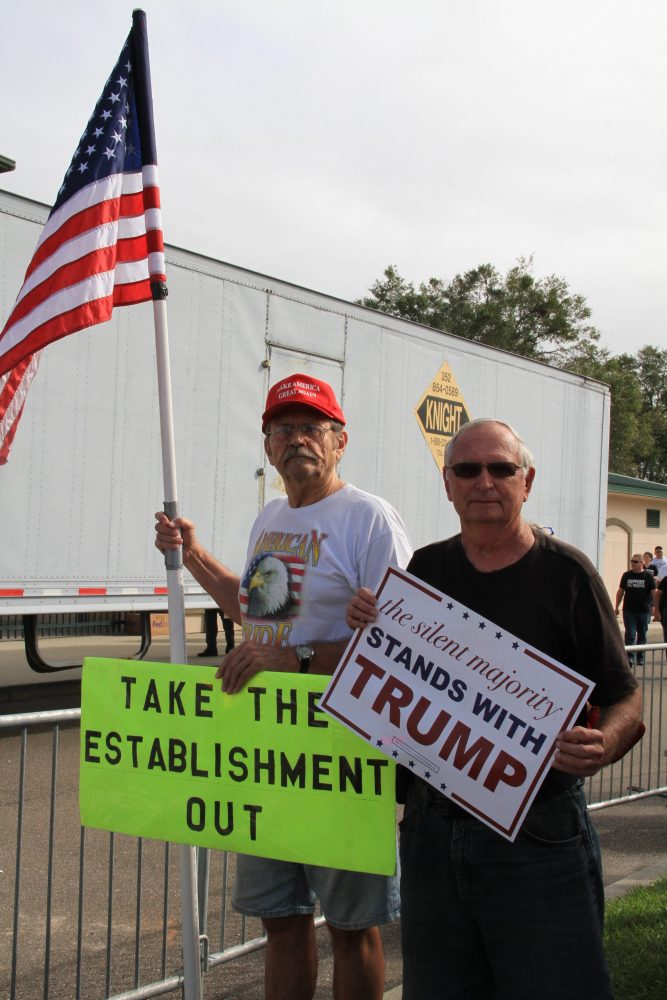"John Nawrocki (left) and David Maquis stand outside the Trump rally on Wednesday morning. Nawrocki, who identifies as a member of the Tea Party, said that supporting Trump is just his latest form of protest against the government. ""I've been fighting against Obama for the past eight years now,"" he said, ""and I'm not stopping any time soon."""