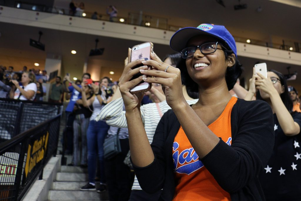 "Kalyani Hawaldar, 22, a graduate student at the University of Florida, captures a video of President Obama during his speech. ""It's been one of my dreams to hear him speak,"" she said. (Rachel Wang/WUFT News)"