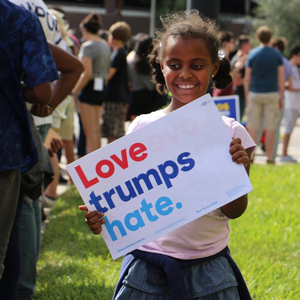 "Senait Williams dances with a ""Love trumps hate"" sign as her family waits in line to enter CFE area. (Rachel Wang/WUFT News)"