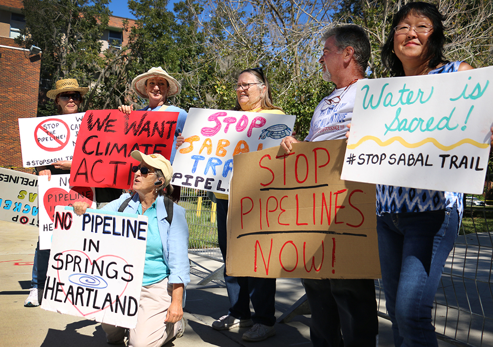 """At the rally entrance, Christine Santilo (left), Merrillee Malwitz-Jipson, Joanne Tremblay, Laverne Hodge, Mitch Allen and Lisa Allen protest the construction of the Sabal Pipeline. """"They don't understand the dangers of these pipelines,"""" said Mitch Allen, who was concerned about possible leaks and water contamination."""