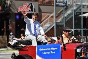 Gainesville Mayor Lauren Poe waves to the crowd during the start of the UF Homecoming Parade. (Grace King/WUFT News)