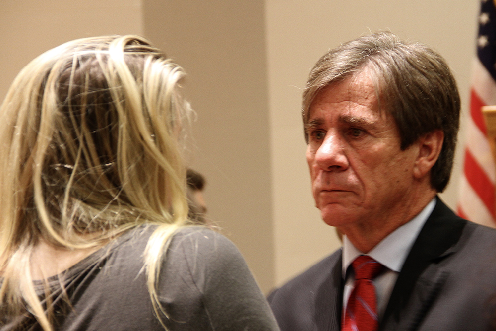 Rod Smith listens to a debate attendee Tuesday night. (Catie Flatley/WUFT News)