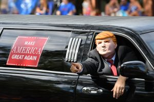 Supporters of Republican presidential nominee Donald Trump ride down University Avenue in a limousine during the parade. (Grace King/ WUFT News)