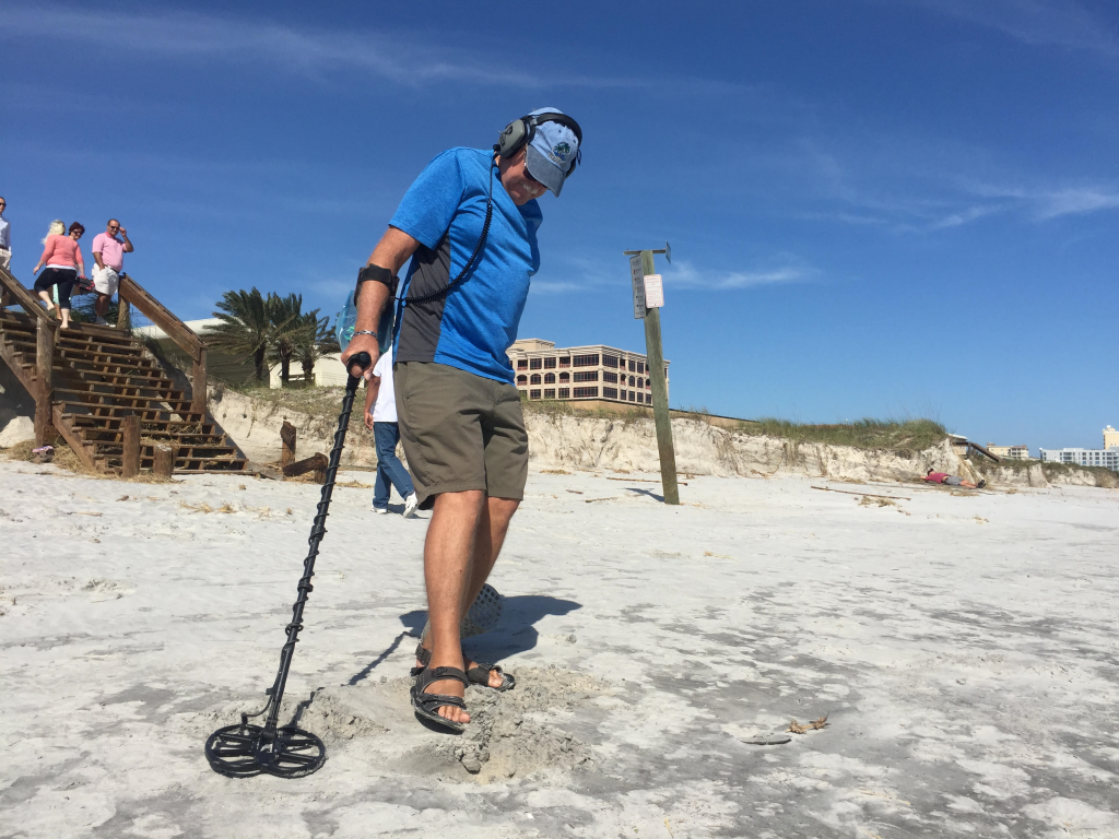 Jacksonville resident Martin Schramm, 63, uses his metal detector Sunday to collect objects buried in the sand.  (Sara Girard/WUFT News)