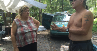 "Rosalie Sherman (left) and Doug Ashcraft, who live together at the Sweetwater Branch homeless camp, discuss their plans for the future after receiving a notice to vacate the camp by Oct. 10. ""This is our home,"" Sherman said, crying. ""This is the only home we knew."" (Michaela Steakley/WUFT News)"