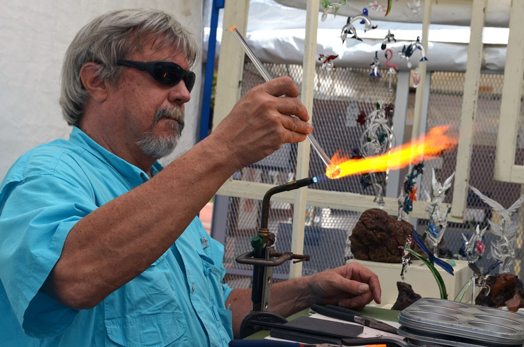 Jay McIver hand blows a glass swizzle stick in his tent as shoppers watch Saturday at the Gainesville Downtown Festival and Arts Show. McIver, a local artist, has blown glass for over 30 years. (Photo by Virginia Annable)