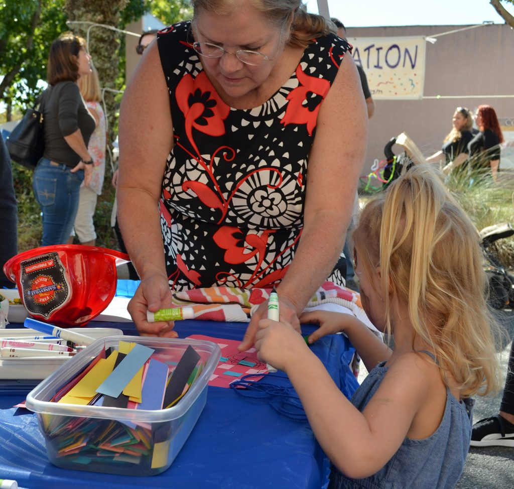 Four-year-old Dylan makes a paper basket with Lenore at the Alachua County School Board tent Saturday after getting her face painted. The tent volunteers helped kids do crafts in the children's area of the Gainesville Downtown Festival and Arts Show. (Photo by Virginia Annable)