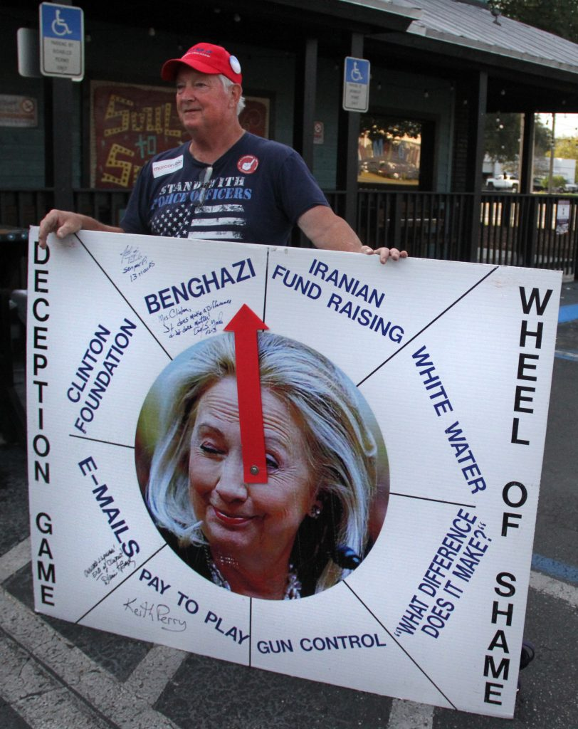 "Ronnie Stewart, a volunteer at the event, said he supported Rubio because ""He's a very fine Christian conservative -- and that sums it up."" Stewart made the ""Hillary Clinton wheel of shame"" and brings it to campaign events to get candidates to sign the board -- he already has Keith Perry and Ted Yoho's signature. (Antara Sinha/WUFT News)"