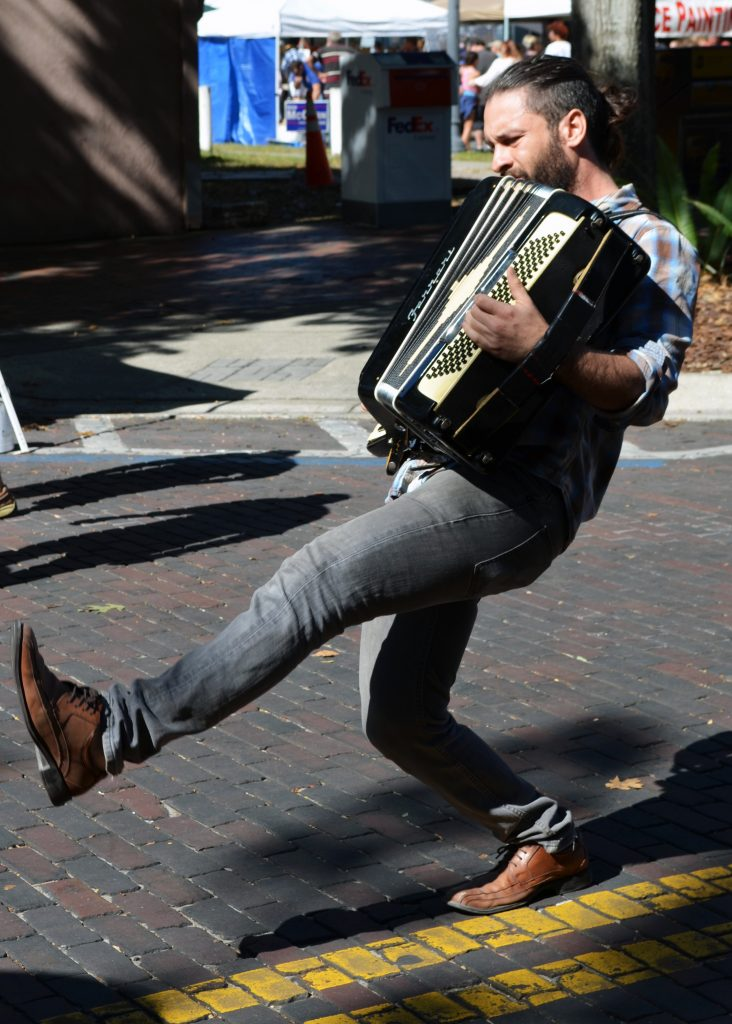 Nick Caputo of the local band, Passerby, plays the accordion, Saturday, in front of the Hippodrome at the Gainesville Downtown Festival and Arts Show. He and bandmate Ernie Williams, who plays the Tuba, performed for tips as passersby listened to the instrumental music. (Photo by Virginia Annable)