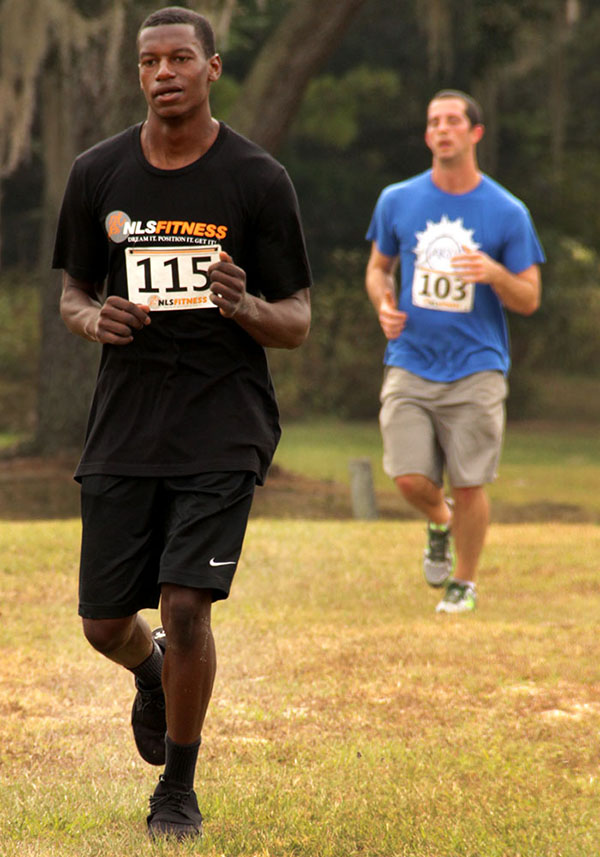 Palatka High School's quarterback James Campbell (left), runs toward the next obstacle during the 5K run. (Photo by Neosman Flores/WUFT News)