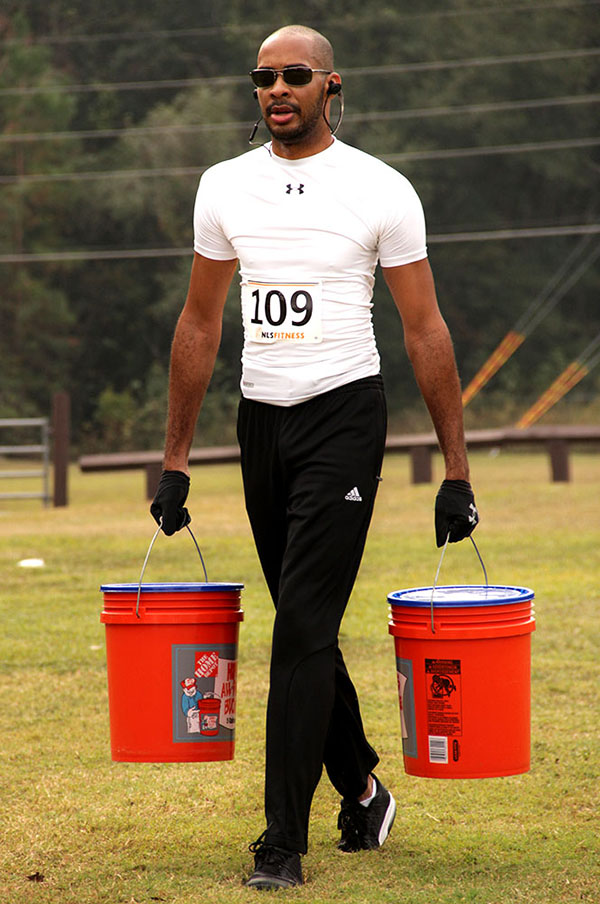 Brian Singleton carries two buckets full of water during the 5K run and obstacle course. (Photo by Neosman Flores/WUFT News)